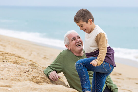 Funny boy and his grandfather on the beach