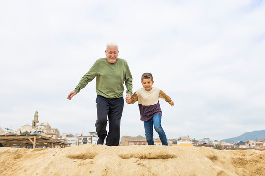 Little boy and his grandfather running on the beach