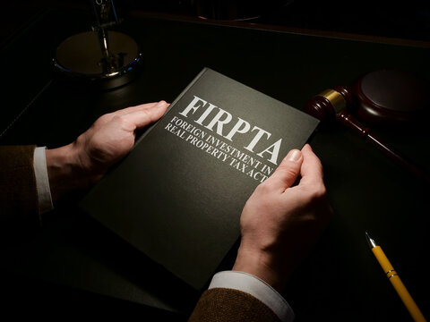 Man holds Foreign Investment in Real Property Tax Act FIRPTA law.