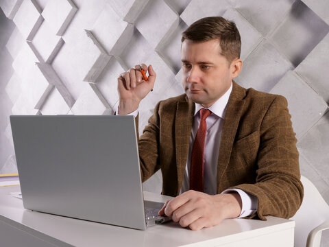 Manager with pen and papers reads data on a laptop screen.