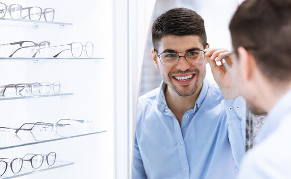 Portrait of happy young guy wearing spectacles near mirror