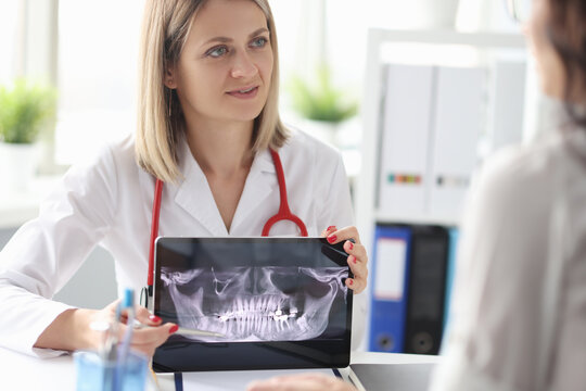 Woman doctor showing 3d picture of teeth on tablet screen