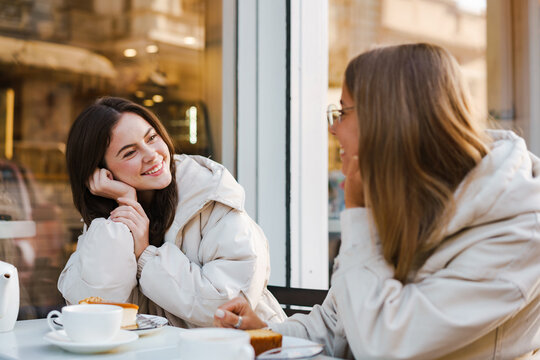 Two cheerful attractive women friends having tea and cakes