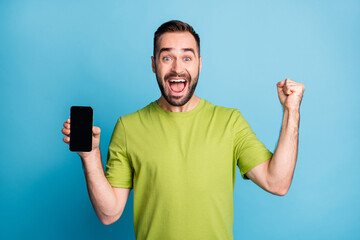 Photo of amazed happy young man raise fist hold smartphone screen empty space isolated on pastel blue color background Wall mural