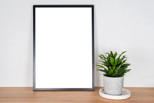 Black wooden vertical frame with white blank card and green plant in concrete pot on wooden table on light gray wall background. Mockup, template for your design, free copy space for text.
