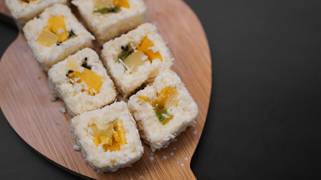 Sushi delivery. Sweet rolls made from rice, pineapple, kiwi and mango. Rolls on a black background
