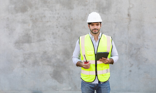 Hispanic or Middle Eastern people. Portrait Of Construction Worker holding red radio and digital tablet isolate on gray cement background. Project engineer On Building Site.