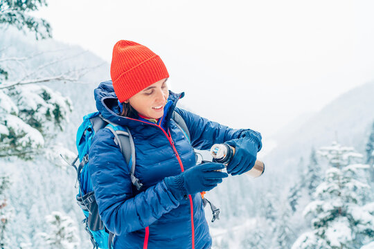 Smiling Woman dressed warm down jacket pouring a hot drink from thermos flask to mug while she has a break on trekking winter mountains route. Active people in the nature concept image.