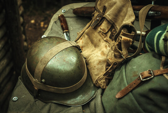 Military equipment of the Second World War. An iron helmet, a cloth bag, a backpack, and a knife. Photo in retro style.