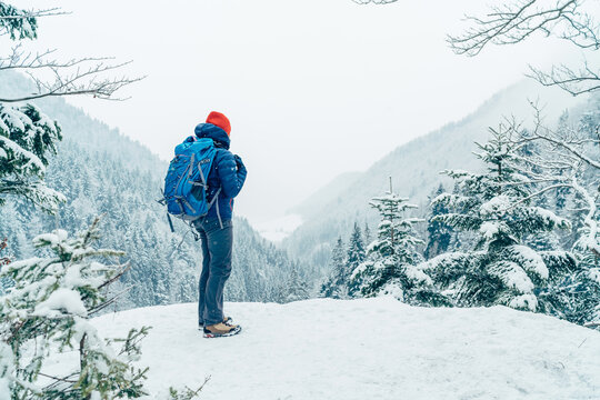 Female backpacker with backpack dressed warm down jacket enjoying snowy mountains landscape while she trekking winter mountain forest route. Active people in the nature concept image.