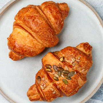 Freshly baked homemade croissants for breakfast. Traditional and whole-grain croissant with pumpkin seeds in a gray plate on a concrete or stone background. Selective Focus, square picture