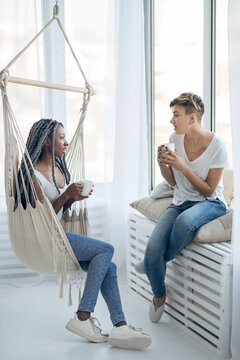 Two girls having coffee in a light room and talking