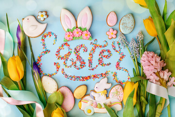 Food Lettering EASTER Colorful easter cookies and flowers tulip on blue background, assortment...