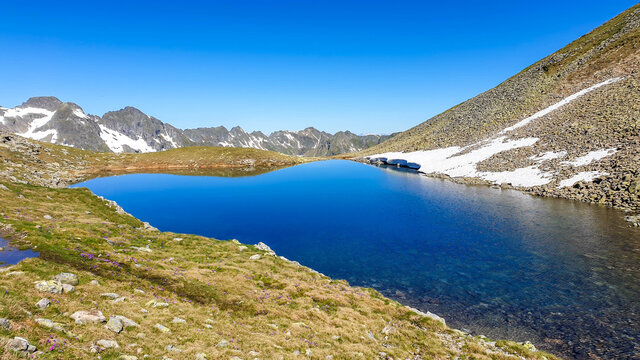 Clear, navy blue lake hiding between tall mountain peaks. Some of the slopes are still covered with snow. In the back here is another mountain range. Clear and bright day. Perfect condition for hiking