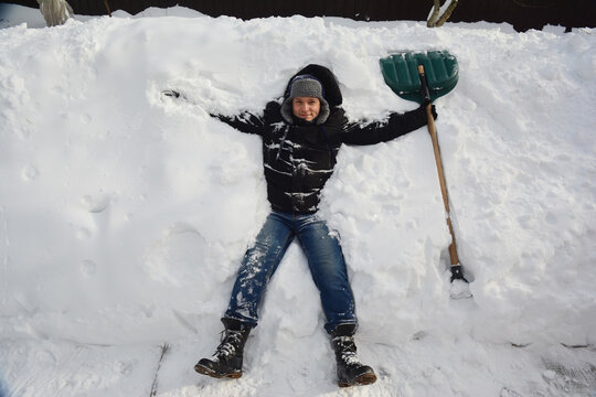 How to avoid heart and back pain while shoveling snow. A man is resting on a huge pile of snow with a snow shovel after shoveling, removing a lot of snow in the backyard of the house and a sidewalk.