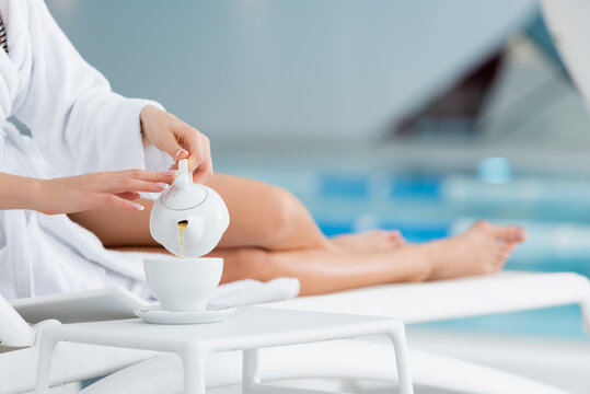Cropped view of woman in bathrobe pouring tea in cup on deck chair in spa center on blurred background