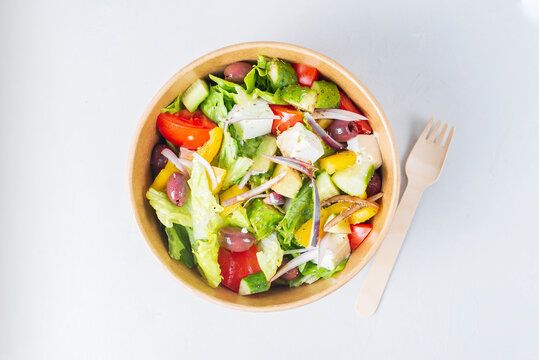 Diet Greek salad with feta, tomatoes, greens on light background top view. Healthy lunch. Food delivery in disposable plate of craft paper. Eco-friendly carton packaging environment protection