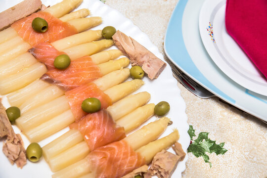 white asparagus wrapped in smoked salmon with tuna and olives. refreshing salad