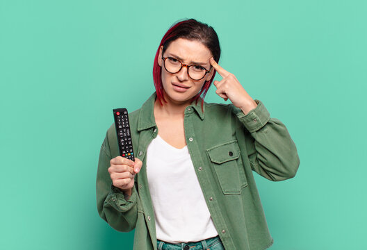 young attractive red hair woman feeling confused and puzzled, showing you are insane, crazy or out of your mind and holding a tv remote control