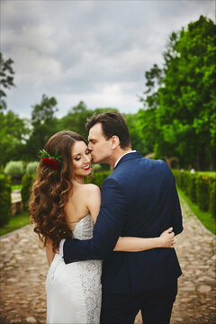 Stylish couple of happy newlyweds posing in the park on their wedding day. Perfect couple, bride and groom posing and kissing