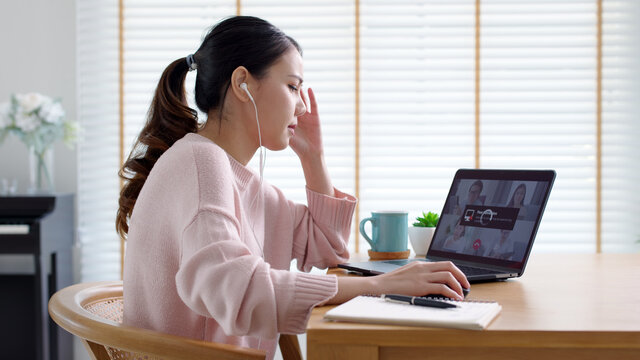 Back rear view young asian woman employee work from home using computer notebook videocall meeting conference angry annoy with low poor unreliable internet wifi connection problem issue outage.