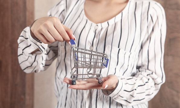 Young woman holding toy shopping cart.