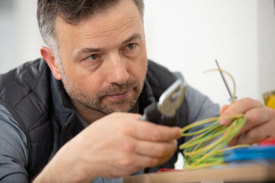 close view of male electrician using wire cutters