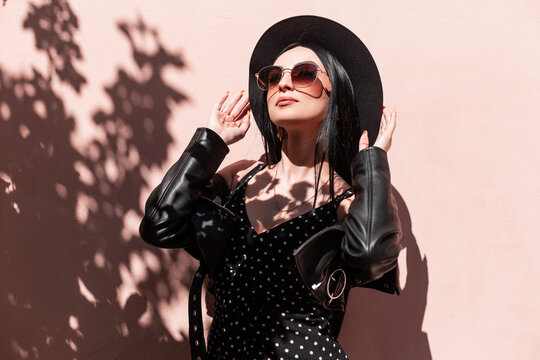 Glamorous young brunette woman in beautiful fashionable black clothes straightens hat outdoors. Luxurious sexy girl in dress in leather jacket in sunglasses posing and enjoys sunlight. Summer style.