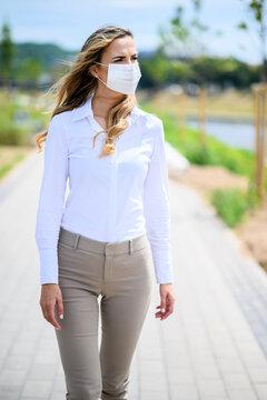 Beautiful girl alone young woman walking outdoor and wearing a mask, coronavirus concept
