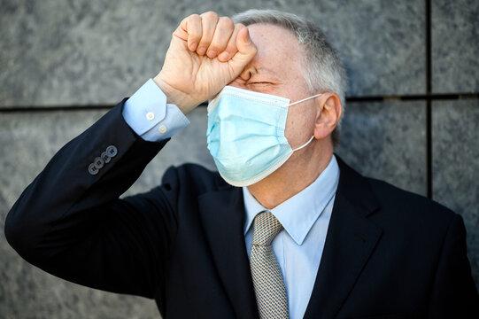 Desperate businessman wearing a mask against coronavirus, financial crisis concept