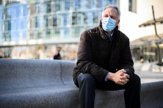 Senior man sitting outdoor wearing a protective mask against coronavirus pandemic