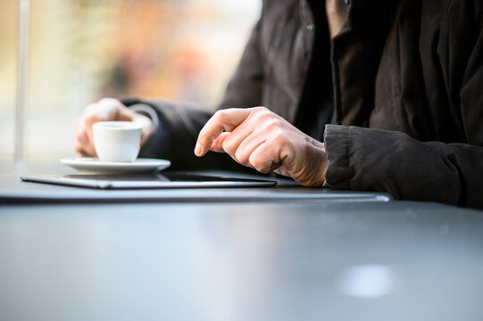 Man having coffee and using tablet