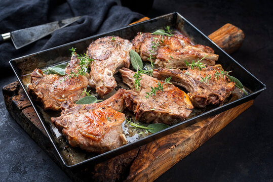 Traditional barbecue dry aged veal chops served as close-up in a rustic tray on a black board