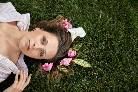 A woman lies on the lawn in the spring, flowers in her hair, looking at the camera. The concept of natural cosmetics. Light striped shirt. Short hair, square.