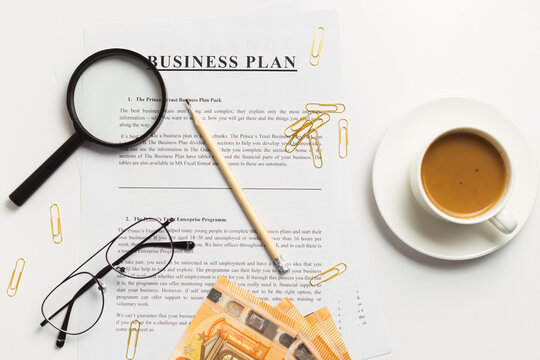 Flat lay of business plan documents with money, glasses, coffee cup, paper clip and supplies on white table desk