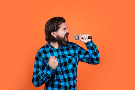 vocal warm up. brutal guy in karaoke club. male singing in mic. handsome hipster on party. music. mature man sing a song. vocal classes. style of music. bearded man sing in microphone