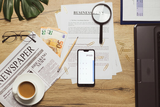 Flat lay of business plan documents on workplace. Money, newspaper, glasses, coffee cup, paper clip and supplies on wooden table desk.