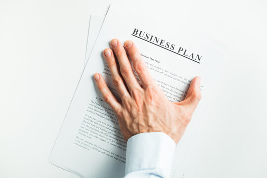 Male hand covers the document on the table. Final decision.