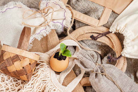 Egg with green fragile sprout on background of eco-friendly reusable natural bags. Zero waste, plastic free concept