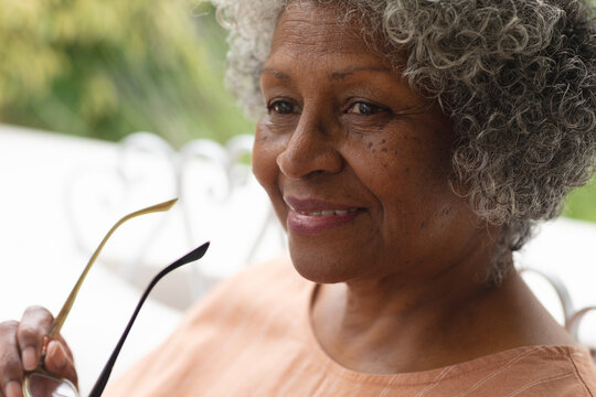 Portrait of african american senior woman holding glasses smiling while sitting on porch