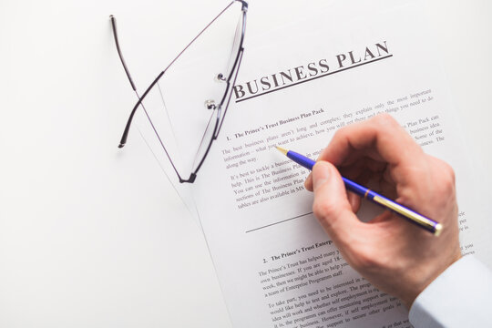 Business plan scrutiny concept. Flat lay on white table.