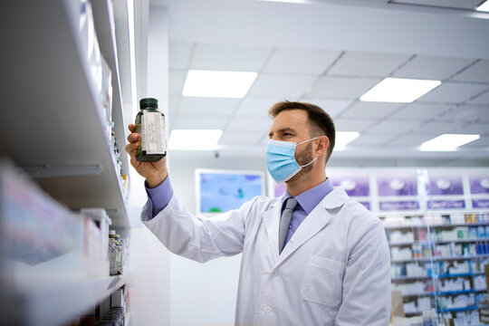 Pharmacist wearing face mask and taking vitamins from the shelf in pharmacy store during covid-19 pandemic. Healthcare and medicine.