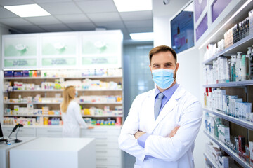 Portrait of pharmacist wearing face mask and white coat standing in pharmacy store during corona virus pandemic.