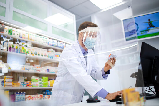 Pharmacist wearing face shield and white coat selling vitamins in pharmacy store during corona virus pandemic.