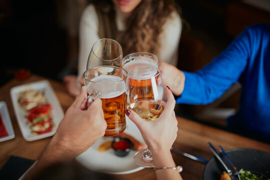Group of friends celebrating in restaurant and toasting with beer.