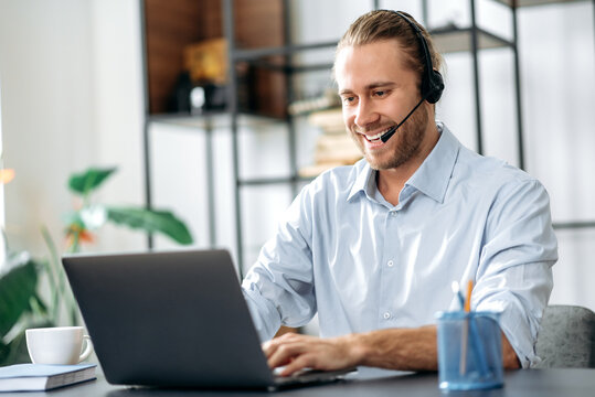 Joyful young adult male manager or call center worker in headset is looks at the laptop screen, having online business meeting. Successful employee talking online with colleagues