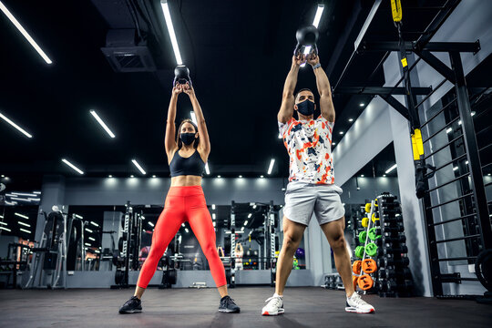 Muscular sporty couple in shape with face masks lifting kettlebells while standing in gym. Bodybuilding, indoor fitness, healthy lifestyle