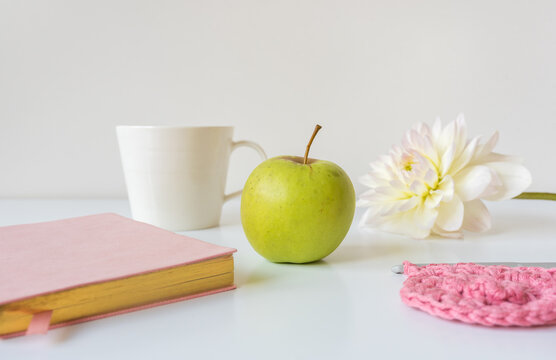 Closeup of green apple on table with self care items in background including crochet, flower, cup, journal (selective focus)