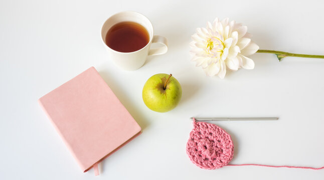 High angle closeup of green apple on table with self care items including crochet, flower, cup, journal (selective focus)