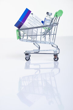 Shopping cart with Vaccine box and vial with Sputnik V vaccine Gam-COVID-Vac on white table with reflection.